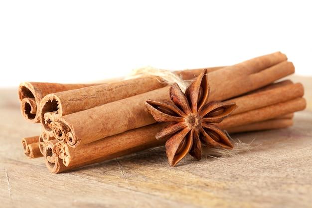 Paus de canela perfumados inteiros e anis estrelado contendo juntos em uma velha tábua de madeira