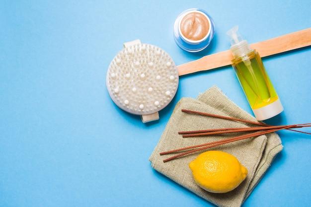 Paus de incenso, limão, óleo corporal, esfoliante caseiro natural em uma jarra e escova para massagem a seco em uma superfície azul