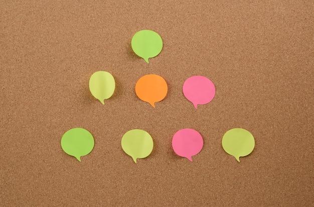 Paus redondos multicoloridos são colados na placa de cortiça marrom, copie o espaço