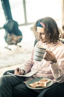 Pausa para o almoço. focado músico de cabelos escuros comendo sanduíches de manteiga de amendoim por perto enquanto escrevia no álbum