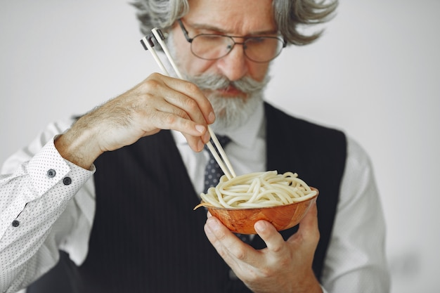 Pausa para o almoço. homem elegante no escritório. empresário de camisa branca. o homem come macarrão.