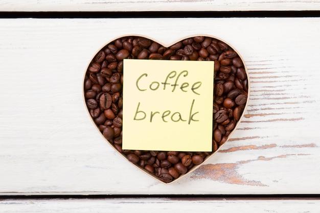 Pausa para o café e o conceito de amor. grãos de café torrados marrons em forma de coração na superfície de madeira branca.