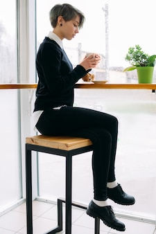 Pausa para o café. jovem bonito trabalhador de escritório ou mulher de negócios, sentado no café, bebendo uma bebida quente.