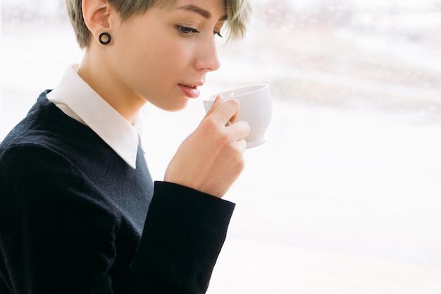 Pausa para o café. trabalhador de escritório ou mulher de negócios bebendo bebida quente em um copo branco