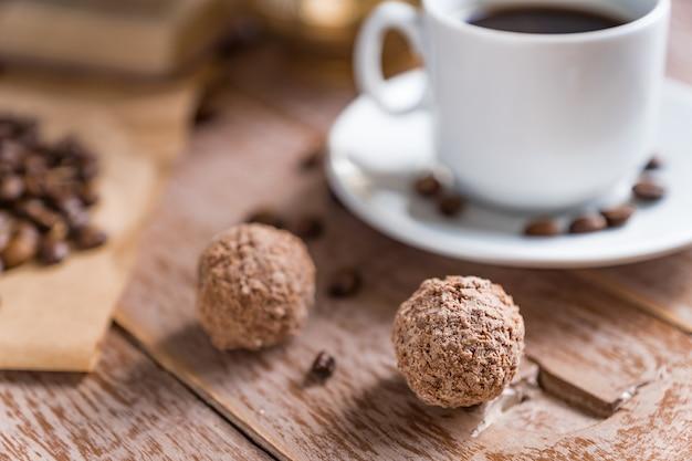Pausa para o café. xícara de café turco recém-breved, bolas de chocolate e livro na mesa de madeira