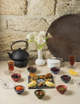 Pausa para o chá com chaleira preta, copos de chá e rendição doce