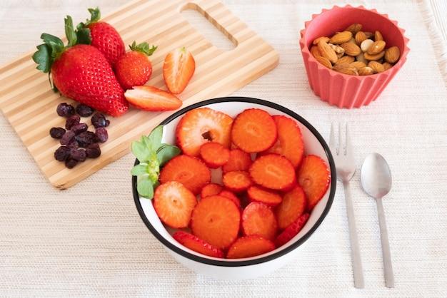 Pausa saudável com frutas frescas como morango, amêndoas e frutas vermelhas. alimentação saudável