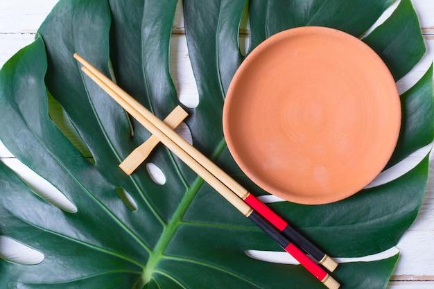 Pauzinho e travessa de cerâmica artesanal. conceito de comida asiática.