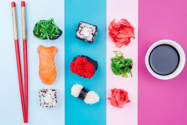 Pauzinhos ao lado de rolos de sushi e molho