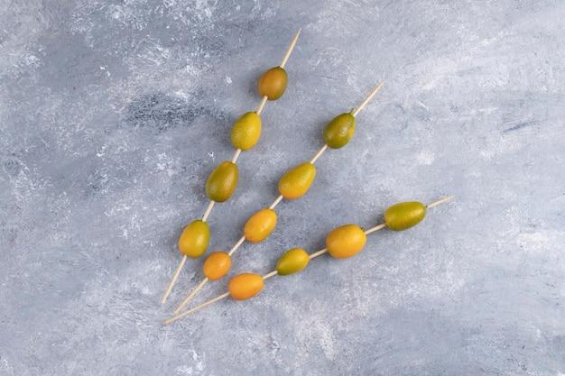 Pauzinhos com kumquats frescos em uma bola de gude.
