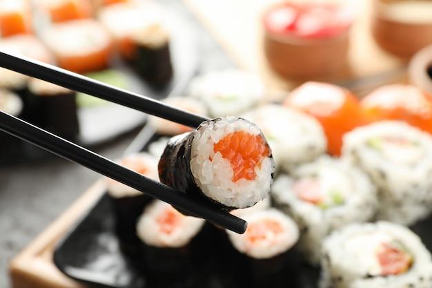 Pauzinhos com rolo de sushi delicioso. comida japonesa