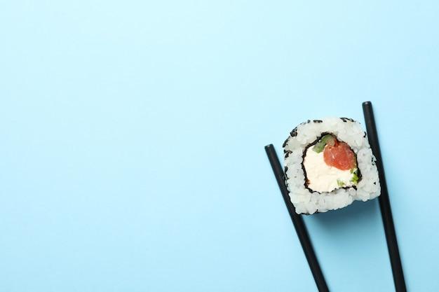 Pauzinhos com rolo de sushi na mesa azul. comida japonesa