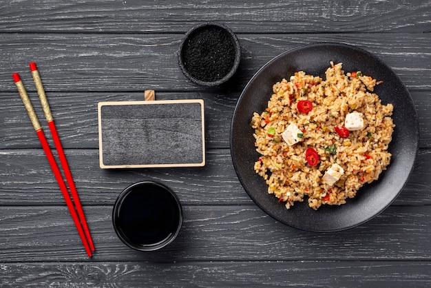 Pauzinhos de alto ângulo e arroz com legumes no prato com lousa em branco