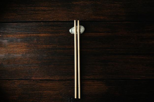 Pauzinhos de madeira para comida asiática chinesa no fundo escuro de madeira e pedra