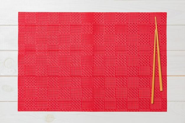 Pauzinhos de sushi com toalha de mesa vermelha vazia, guardanapo em branco de madeira
