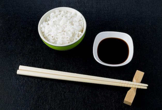 Pauzinhos de sushi japonês sobre tigela de molho de soja, arroz em fundo preto