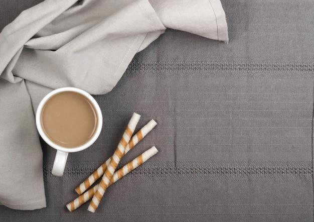Pauzinhos de wafer de chocolate e xícara de café com leite na vista superior do fundo cinza