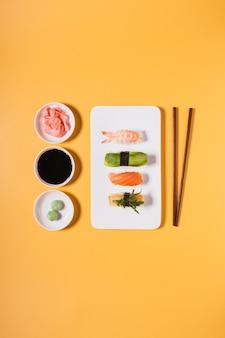 Pauzinhos e condimentos perto de sushi variado