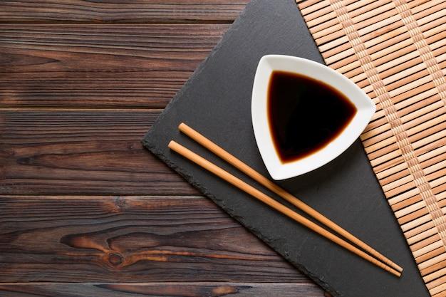 Pauzinhos e molho de soja na placa de pedra preta, de madeira com espaço de cópia