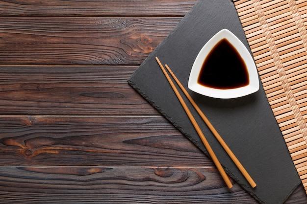 Pauzinhos e molho de soja na placa de pedra preta, fundo de madeira com espaço de cópia.