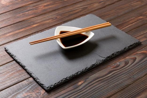 Pauzinhos e molho de soja na placa de pedra preta