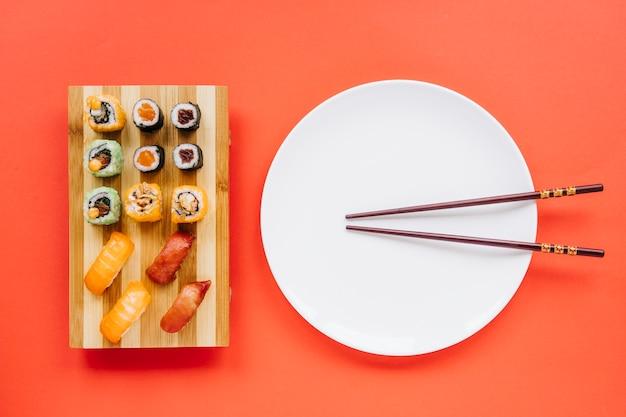 Pauzinhos e prato perto de sushi