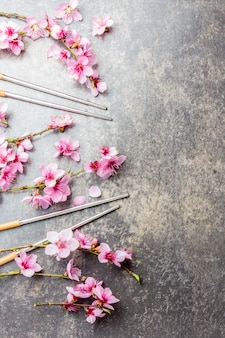 Pauzinhos e ramos de sakura na pedra cinza