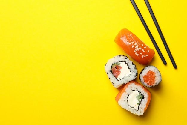 Pauzinhos e rolos de sushi na superfície amarela. comida japonesa