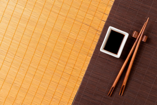 Pauzinhos e tigela com molho de soja em dois bambu esteira blak e amarelo vista superior com espaço de cópia