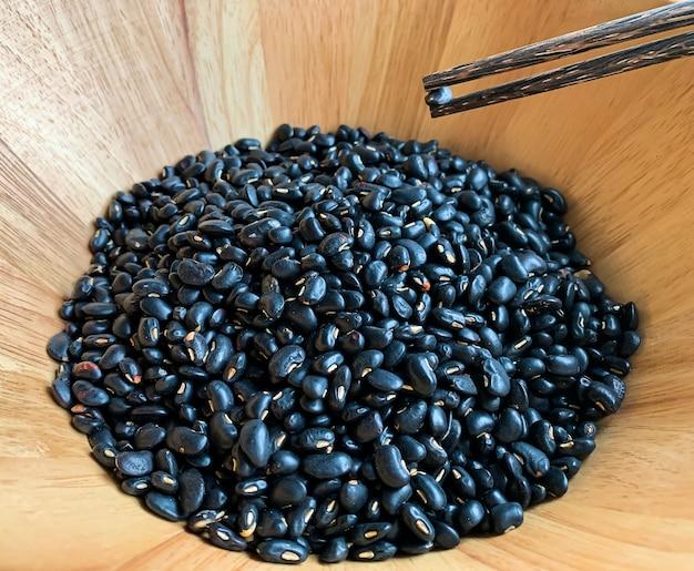 Pauzinhos em cubos de feijão preto em uma tigela de madeira, propriedades ajudam a desintoxicar e nutrir os rins também. devido à presença de flavonóides e antocianinas, ricos em proteínas, impedindo a anemia devido a i
