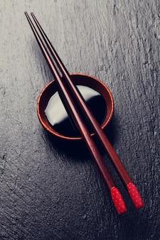 Pauzinhos japoneses de sushi sobre uma tigela de molho de soja em fundo de pedra preta
