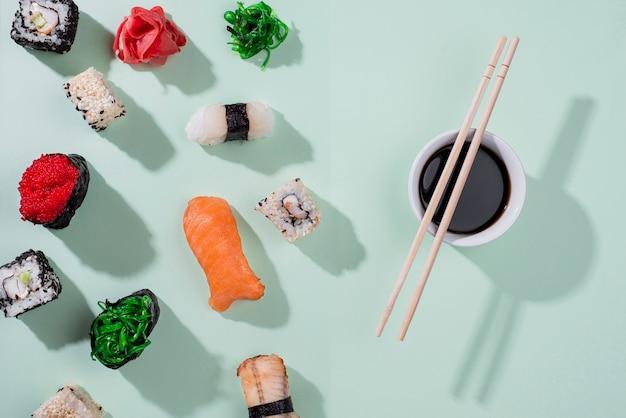 Pauzinhos leigos planos e rolos de sushi para o dia do sushi