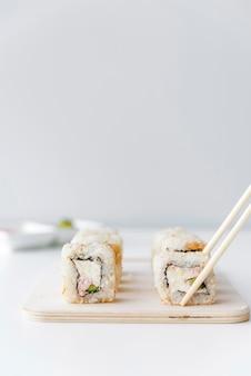 Pauzinhos pegando rolo de sushi