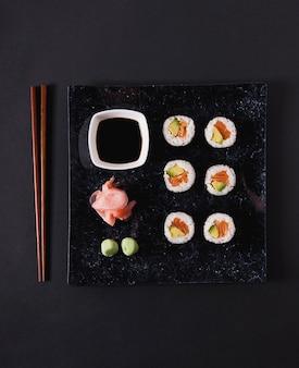 Pauzinhos perto da placa com sushi e condimentos