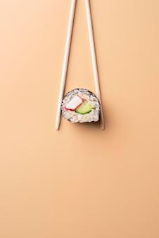Pauzinhos planos segurando sushi
