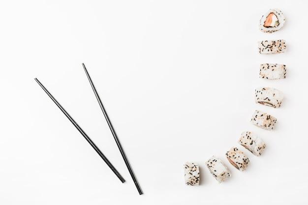 Pauzinhos pretos com rolos de sushi no fundo branco