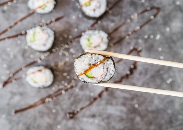 Pauzinhos segurando o rolo de sushi com molho