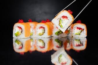 Pauzinhos segurando o rolo de sushi Filadélfia no fundo preto feito de salmão