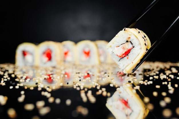 Pauzinhos segurando o rolo feito de nori, arroz marinado, philadelphia, queijo