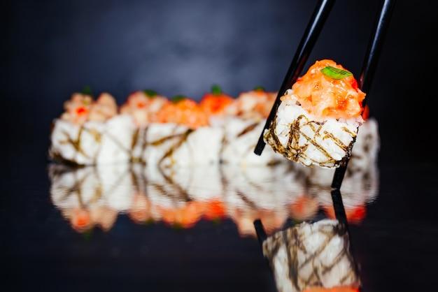 Pauzinhos segurando rolo tobica feito de nori, arroz marinado, queijo, cucumbe
