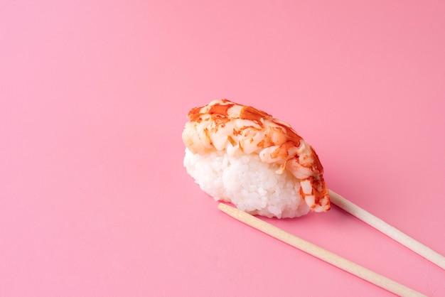Pauzinhos segurando sushi em ângulo alto