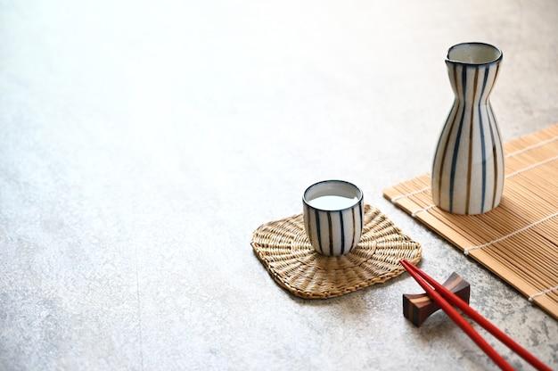 Pauzinhos vermelhos e saquê japonês bebem estilo oriental em cima da mesa, copyspace