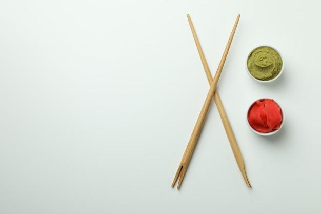 Pauzinhos, wasabi e gengibre em conserva no branco