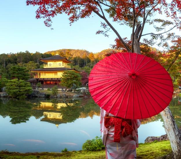 Pavilhão dourado ou templo kinkakuji com folhas de outono vermelhas em kyoto, japão