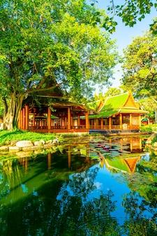 Pavilhão em estilo tailandês com lago e árvore no jardim
