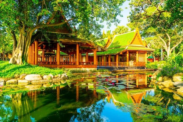 Pavilhão em estilo tailandês com lago e árvore