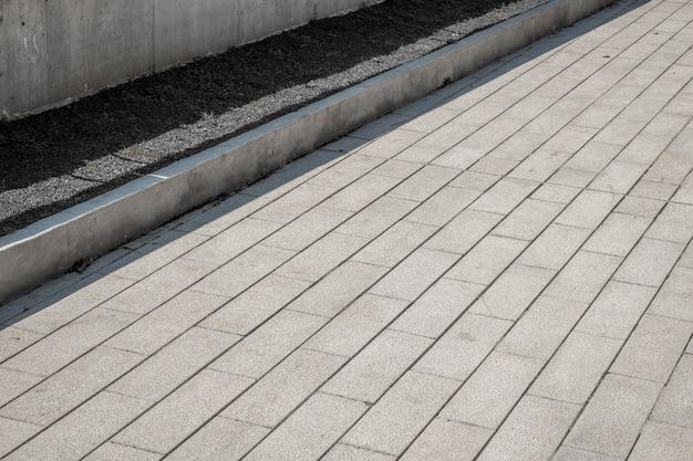 Pavimentação piso de tijolos vista em perspectiva de pedra de pavimentação textura monótona de ladrilhos de tijolo cinza