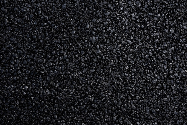 Pavimento asfáltico japonês com uma bela textura preta e iluminado por uma luz suave.