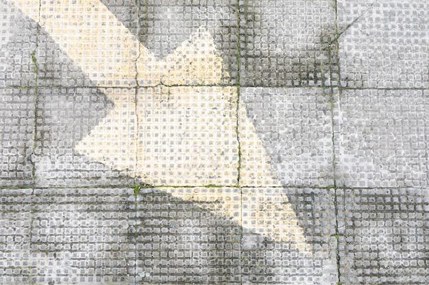 Pavimento áspero de concreto com seta pintada