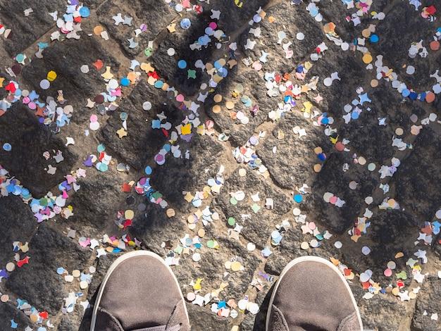 Pavimento coberto com confetes coloridos e sapatos